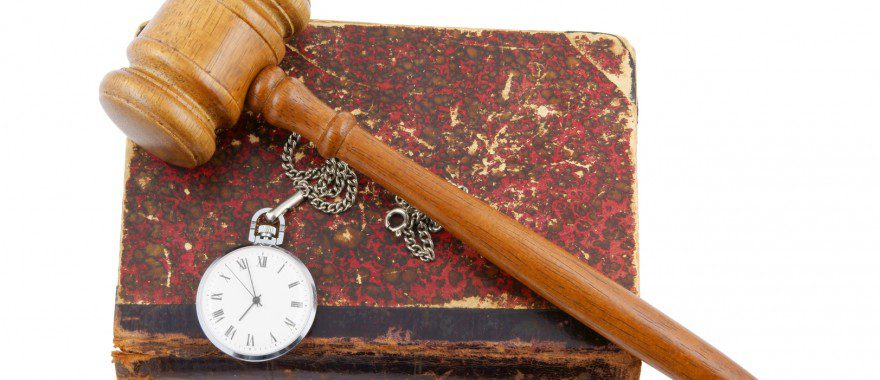 Judge's gavel and very old legal book with watch